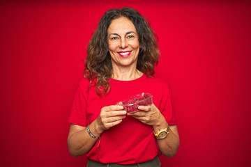 Wall Mural - Middle age senior woman eating raspberries over red isolated background with a happy face standing and smiling with a confident smile showing teeth