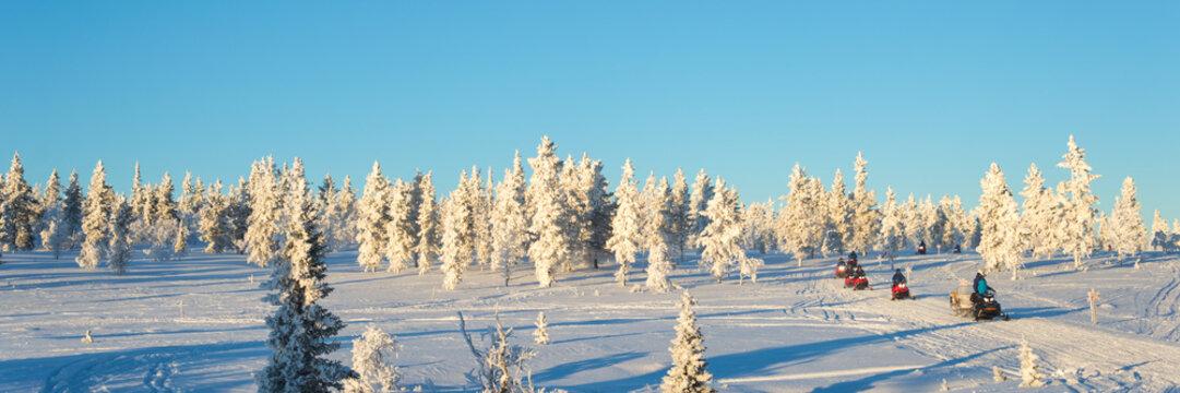Group of snowmobiles in Lapland, near Saariselka, panoramic winter background, Finland