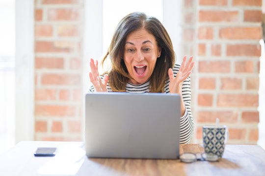 Middle age senior woman sitting at the table at home working using computer laptop very happy and excited, winner expression celebrating victory screaming with big smile and raised hands