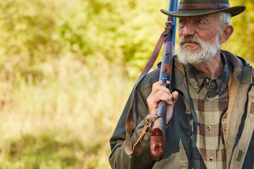 Poster de jardin Chasse Senior caucasian man with hunting gun looking away, man with grey beard wearing hunting clothes outdoors. Forest background