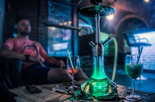 Budapest, Hungary - August 29, 2019: Tall chairs near the bar and a hookah on the table. Cafe interior in the old basement of a house in Budapest. Nightlife and entertainment in the capital of Hungary