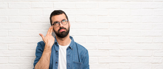 Handsome man with beard over white brick wall with problems making suicide gesture