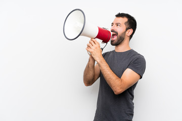 Young handsome man over isolated white background shouting through a megaphone