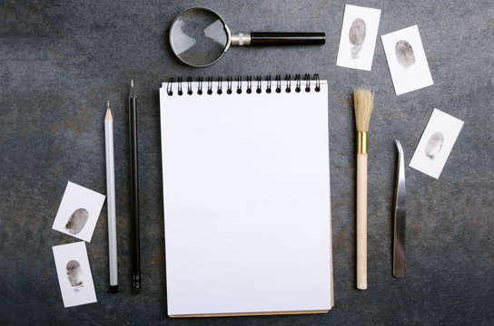 Blank notebook, fingerprint, magnifying glass, pencils and other tools for criminal investigation
