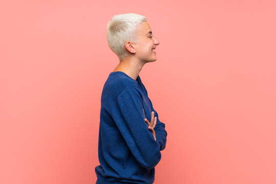 Teenager girl with white short hair over pink wall in lateral position