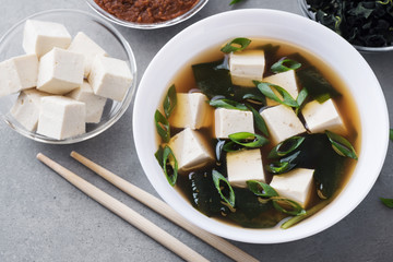 Bowl with miso soup, wakame seaweed, miso pasta, tofu and chopsticks on a gray background.