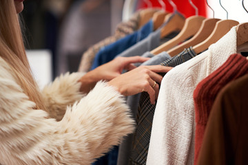 Adult women shopping for clothes in boutique in autumn