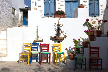 Koufonissia Chora - Traditional white houses in the main street with multicolor chairs. Lesser Cyclades island group, Greece