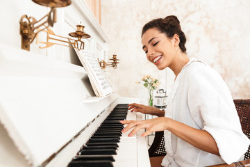 Lady in white shirt play the piano indoors at home.