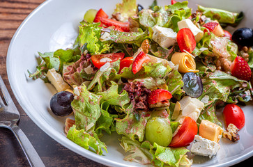 Gourmet green salad with cheese, grape, strawberries and cherry