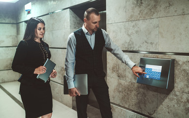 A tall confident caucasian man entrepreneur with a laptop is pushing a button on a modern touchscreen to get an office elevator while his female colleague with a digital tablet is waiting next to him