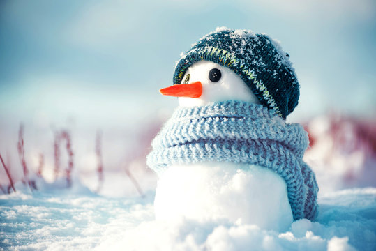 Little cute snowman in a knitted hat and scarf on snow on a sunny winter day. Christmas card