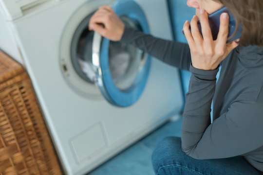 A woman calls a repair service for a breakdown of a washing machine.
