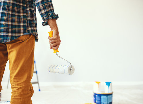 Repair in apartment. Happy man paints wall .