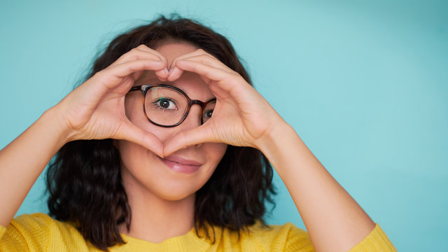 woman in glasses on a turquoise background makes a heart shape with her hands, a symbol of love