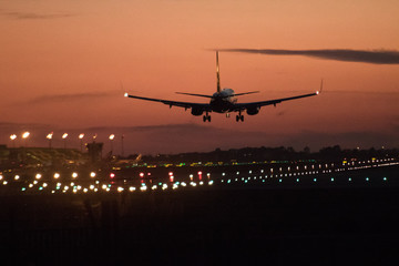 Tuinposter Airplane silhouette landing at the airport during sunser, Barcelona