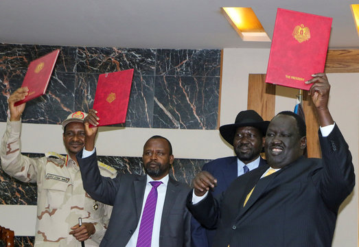 Mohamed Hamdan Dagalo, Alhadi Idris, Salva Kiir and Tut Galwak hold the agreement on peace and ceasefire during the signing ceremony in Juba