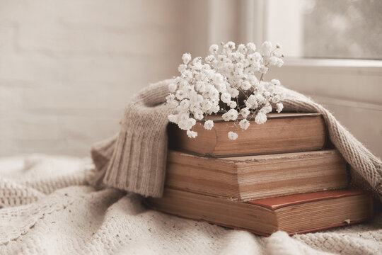 vintage books with airy flowers and a knitted sweater on the table