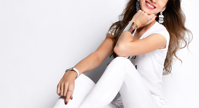 Closeup of beautiful woman sitting in white t-shirt, white pants and metal jewelry happy smiling on white background