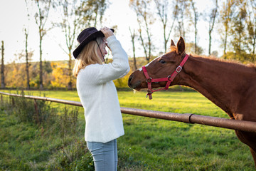 Cowgirl playing with her young horse at farm