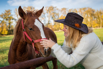 Woman playing with her young horse at pasture