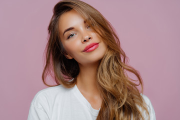 Obraz Portrait of satisfied relaxed young female model tilts head, has makeup, fair hair, dressed in white clothes, poses against purple background, has well cared complexion. People, beauty, face care - fototapety do salonu