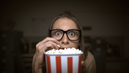 Woman watching a horror movie and eating popcorn