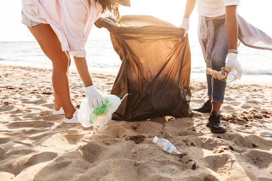 Photo of eco volunteers cleaning beach from plastic garbage together