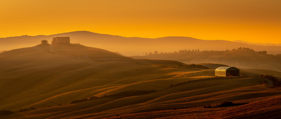 A breathtaking high angle shot of hills with an isolated house under the golden sky. Travel destination Tuscany, Siena, Crete Senesi Fototapete