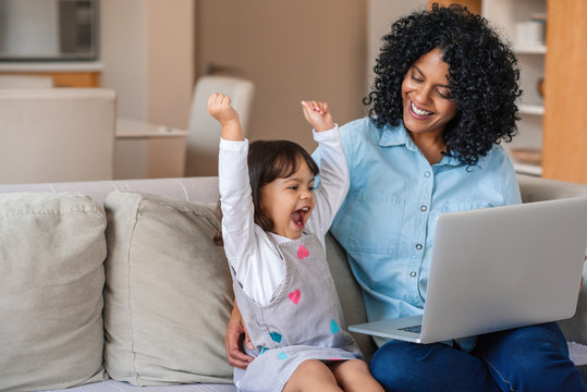 Laughing little girl and mother watching something on a laptop