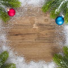 Tannengrün mit Schnee und zwei farbenfrohe Christbaumkugeln auf altem Holz - Weihnachten - Textfreiraum - Vorlage
