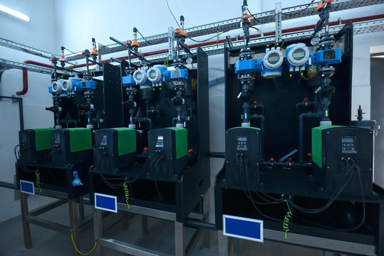 Dosing pumps, tubes, manometers set in the dosing systems hall of the water pumping station
