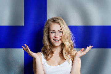 Beautiful happy young woman against the finnish flag background. Live, education and work in Finland