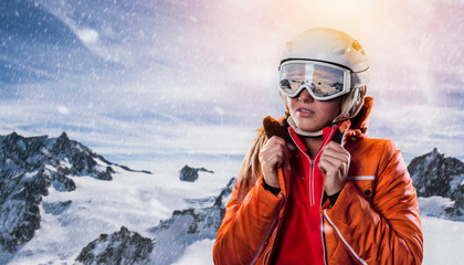 young woman snowboarder wearing winter sports gear in wintry mountains environment enjoys panoramic view