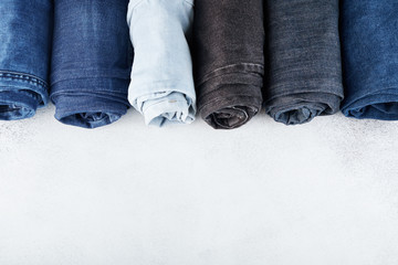 Row of different rolled jeans on white background Wall mural