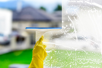 Window cleaner for washing a windows. Hand in yellow glove hold cleaning squeegee.