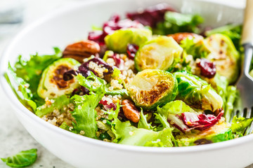 Papiers peints Bruxelles Fried brussels sprouts salad with quinoa, cranberries and nuts in white bowl. Healthy vegan food concept.