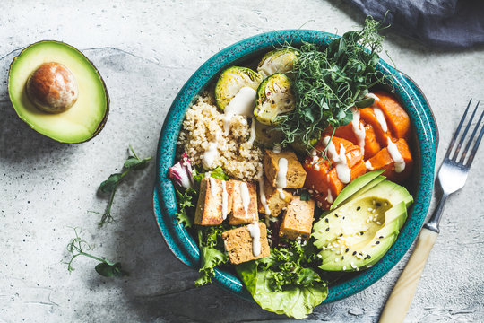 Buddha bowl with quinoa, tofu, avocado, sweet potato, brussels sprouts and tahini dressing, top view. Healthy vegan food concept.
