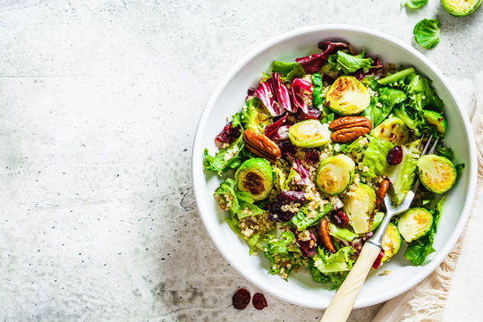 Fried brussels sprouts salad with quinoa, cranberries and nuts in white bowl, top view. Healthy vegan food concept.