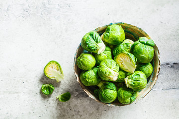 Spoed Fotobehang Brussel Raw brussels sprouts in bowl, gray concrete background, top view. Healthy vegan food concept.