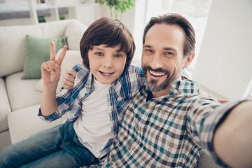 Comfortable weekend vacation with father concept. Close up photo of handsome bearded with teeth smile guy hugging his sweet son taking selfie making v-sign in living room house indoors