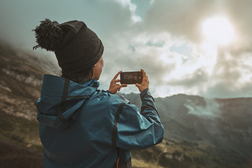 A hiker girl take a pictures on a smartphone in the mountains at sunset