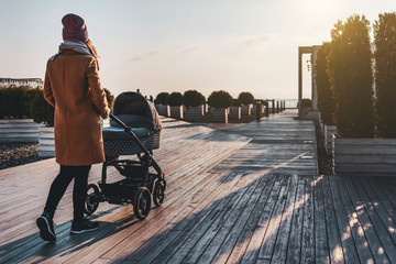 Young woman walking through city park with baby stroller. Warm autumn or spring weather for outdoor activity. Pretty urban architecture and landscape design. Sunset, clouds in sky, sunny day for walk