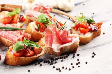 Assorted bruschetta with various toppings. Appetizing bruschetta or crudo crostini. Variety of small sandwiches. Mix bruschetta on table