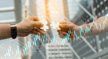 Teamwork,partnership and Social connection in business join hand together concept.Businessman holding jigsaw puzzle with chart.Financial Graph. Stock Market chart.