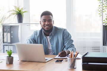 Portrait of smiling black trainee taking notes at new workplace