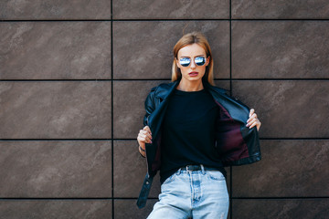 Girl wearing t-shirt, glasses and leather jacket posing against street , urban clothing style. Street photography