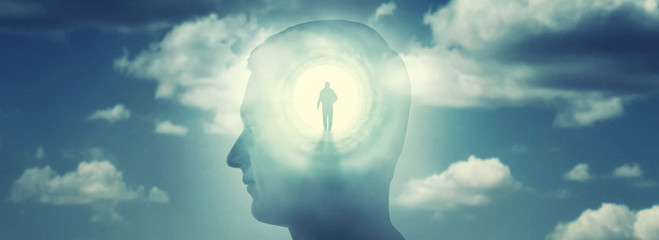 A silhouete of a man with rays of light emanating from the brain as a symbol of the power of thinking. Concept on the topic of psychiatry (bipolar disorder, schizophrenia), psychology, religion etc.