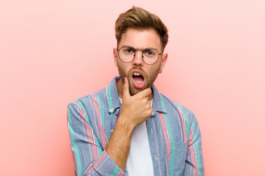 young man with mouth and eyes wide open and hand on chin, feeling unpleasantly shocked, saying what or wow against pink background