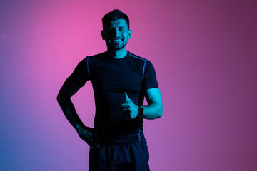 Handsome fitness man in sportwear giving thumb up isolated on pink light background